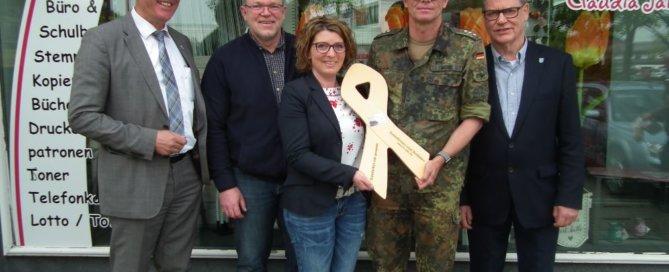 """Im Beisein von Bürgermeister Christian Somoygi und Stadtrat Otmar Bonacker erhält Inhaberin Claudia Janik die """"Gelbe Schleife"""". (Foto: Klaus Böttcher)"""